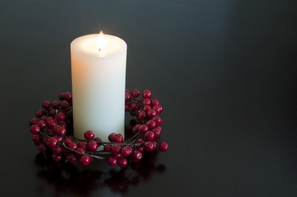 Single burning white Christmas candle with a red berry wreath around the foot glowing in the darkness with copyspace for your seasonal or spiritual message