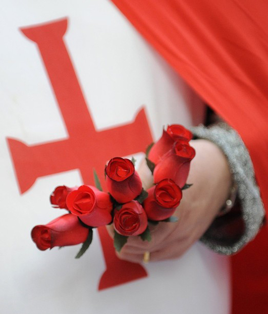 A stall holder holds roses whilst wearing fancy-dress at St. George's Day themed-stalls at a market in the City of London April 23, 2010. REUTERS/Toby Melville (BRITAIN - Tags: ANNIVERSARY SOCIETY)