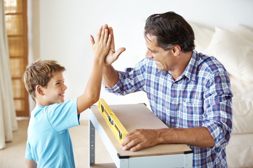 Excited man giving high five to a little boy after completing the work in workshop